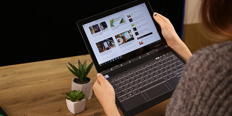 Woman holding laptop on hand