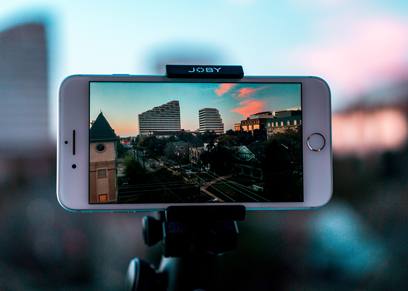 White smartphone making a video of cities with buildings