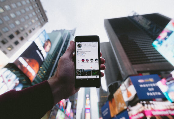 Person holding mobile phone with instagram apps on the screen