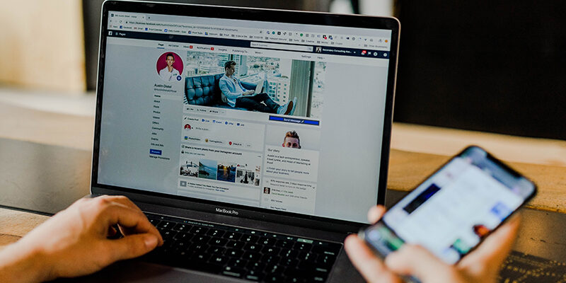 laptop screen flashes Facebook feed while a man holding a cellphone