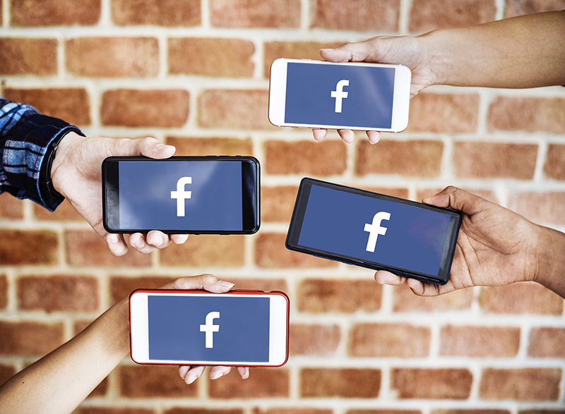 four persons holding smartphones with Facebook icon on each screen