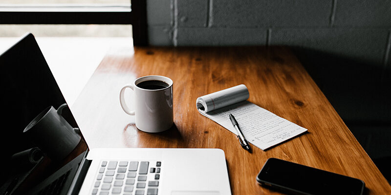 MacBook pro, white ceramic mug, and black smartphone on table
